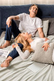 Middle aged couple laughing and lying on bed at home Royalty Free Stock Photos