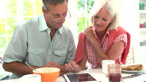 Middle Aged Couple Looking At Digital Tablet Over Breakfast Stock Photo
