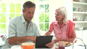 Middle Aged Couple Looking At Digital Tablet Over Breakfast stock video