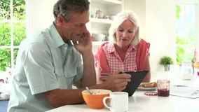 Middle Aged Couple Looking At Digital Tablet Over Breakfast stock footage