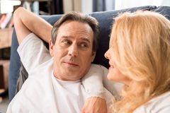 Middle aged couple looking at each other and lying on bed at home Stock Photos