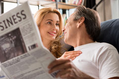 Middle aged couple looking at each other, man with newspaper at home Royalty Free Stock Image