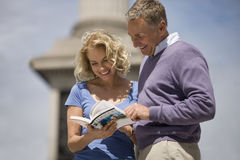 A middle-aged couple looking at a guidebook royalty free stock images
