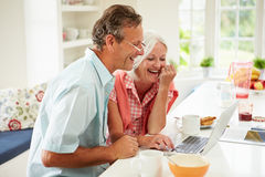 Middle Aged Couple Looking At Laptop Over Breakfast stock photo