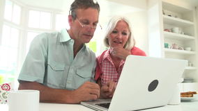 Middle Aged Couple Looking At Laptop Over Breakfast stock footage