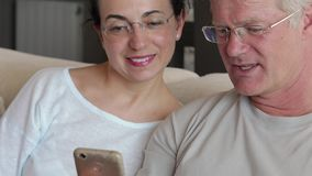 Middle-aged couple looking a mobile phone stock video footage