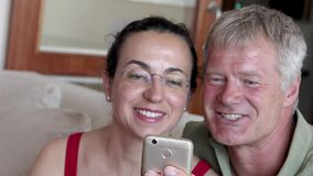 Middle-aged couple looking a mobile phone stock video