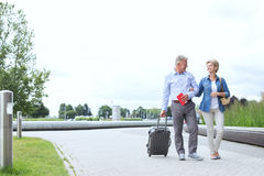 Middle-aged couple with luggage walking on footpath against clear sky Royalty Free Stock Images
