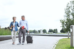 Middle-aged couple with luggage walking on footpath against clear sky Royalty Free Stock Photo