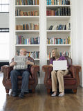 Middle Aged Couple With Newspaper And Laptop At Home Royalty Free Stock Photos