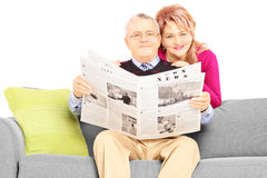 Middle aged couple with newspaper sitting on a couch Royalty Free Stock Photo