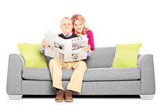 Middle aged couple with newspaper sitting on a sofa Royalty Free Stock Images