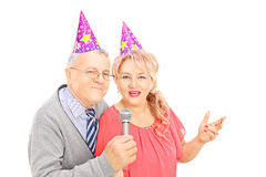 Middle aged couple with party hats singing on microphone Stock Images