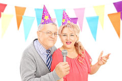 Middle aged couple with party hats singing on microphone Royalty Free Stock Photos