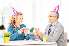 Middle aged couple with party hats sitting and playing cards at Royalty Free Stock Photos