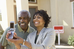 Middle-aged couple photographing in front of new home stock photography