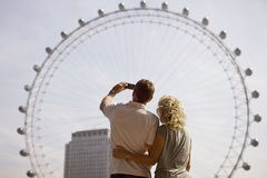 A middle-aged couple photographing the London Eye, rear view Royalty Free Stock Images