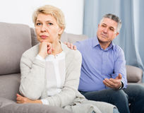 Middle-aged couple quarreling at home with each other. And take offense stock photo