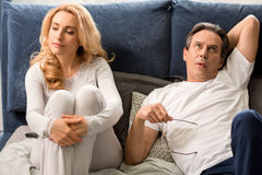 Middle aged couple quarreling and lying on bed at home Stock Photo