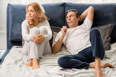Middle aged couple quarreling and lying on bed at home Royalty Free Stock Image