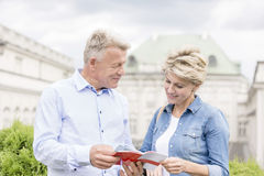 Middle-aged couple reading guidebook outside building Stock Image