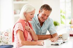 Middle Aged Couple Reading Magazine Over Breakfast royalty free stock images