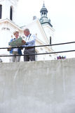 Middle-aged couple reading map by railing outside church Stock Photography