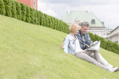 Middle-aged couple reading map while sitting at park Stock Photos
