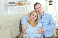 Middle aged couple relaxing on the couch smiling at camera at home in the living room Stock Images