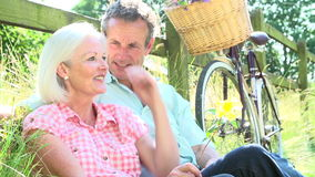 Middle Aged Couple Relaxing On Country Cycle Ride stock video