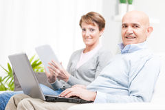 Middle-aged couple relaxing with mobile devices Stock Photos