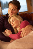 Middle Aged Couple Relaxing On Sofa Stock Photography