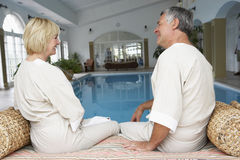 Middle Aged Couple Relaxing By Swimming Pool Royalty Free Stock Photo