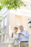 Middle-aged couple reviewing photos on digital camera outside building Royalty Free Stock Photos