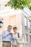 Middle-aged couple reviewing photos on digital camera outside building Royalty Free Stock Photography