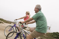 Middle-aged couple riding bicycles Stock Images