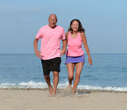 Middle aged couple on sandy beach. Middle aged couple walking on sandy beach hand in hand Royalty Free Stock Photography