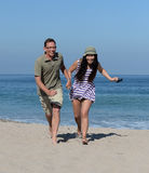 Middle aged couple on sandy beach Stock Images