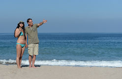 Middle aged couple on sandy beach. Middle aged couple walking on sandy beach hand in hand Stock Image
