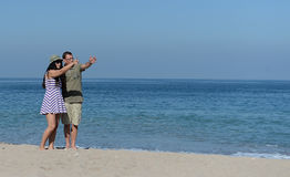 Middle aged couple on sandy beach. Middle aged couple walking on sandy beach hand in hand Royalty Free Stock Photo