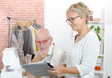 Middle aged couple in a sewing workshop with tablet. A middle aged couple in a sewing workshop with tablet stock image