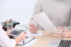 Middle aged couple signing contract at insurance agency. Office Royalty Free Stock Photos