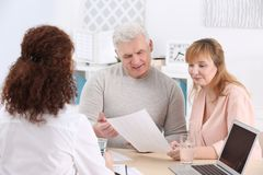 Middle aged couple signing contract at insurance agency. Office Stock Images