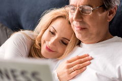 Middle aged couple sitting on bed, man reading newspaper at home Stock Photos