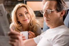 Middle aged couple sitting on bed, man reading newspaper at home Stock Photo