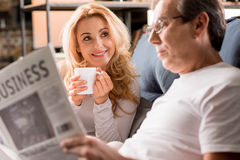 Middle aged couple sitting on bed, man reading newspaper at home Royalty Free Stock Photos