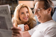 Middle aged couple sitting on bed, man reading newspaper at home Stock Photography