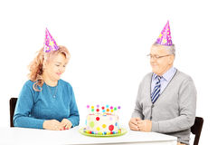 Middle aged couple sitting at birthday party looking at cake Royalty Free Stock Images