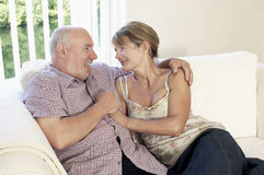 Middle Aged Couple Sitting On Couch Stock Photography