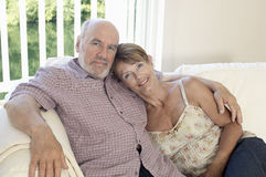 Middle Aged Couple Sitting On Couch Royalty Free Stock Images